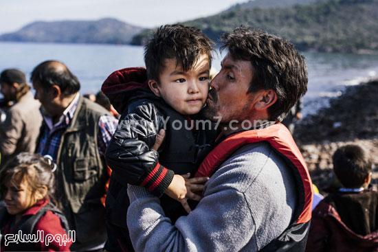 أب يقبل ابنه الصغير فى محاولة للتخفيف عنه  -اليوم السابع -10 -2015
