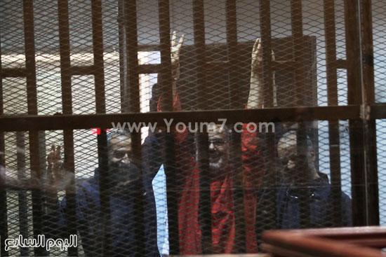 المتهمين يلوحون من داخل قفص الاتهام بعد الحكم  -اليوم السابع -5 -2015