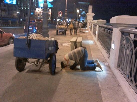 الشاب يؤدى الصلاة بجوار عربة رزقه  -اليوم السابع -5 -2015