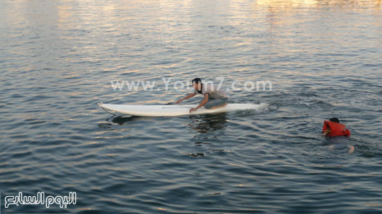 أحد المصطافين يسبح على قاربه فى المياه -اليوم السابع -6 -2015
