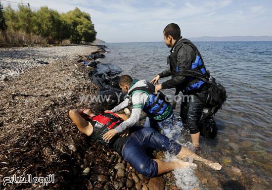 بعض من المهاجرين معه يحاولون إنقاذه. -اليوم السابع -9 -2015