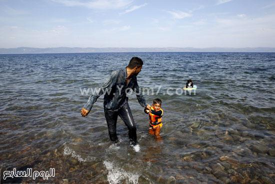 أب يسحب طفله من الماء بعد اقترابهم من الشاطئ. -اليوم السابع -9 -2015