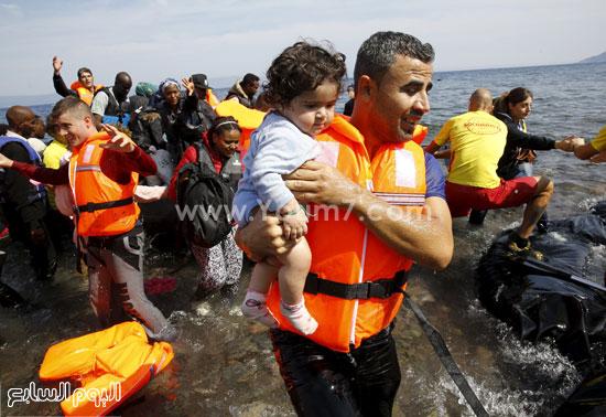 أحد قوات الأنقاذ يحمل طفلا صغيرا. -اليوم السابع -9 -2015