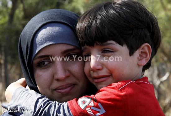 أم تحمل طفلها الذى يبكى من الخوف. -اليوم السابع -9 -2015
