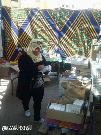 رانيا رئيس فريق المتطوعين بنهر الحياة خلال صرفها بعض الأدوية -اليوم السابع -9 -2015