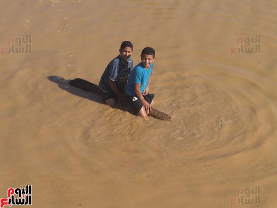 طفلان يركبان أحد جذوع النخيل داخل مياه السيول