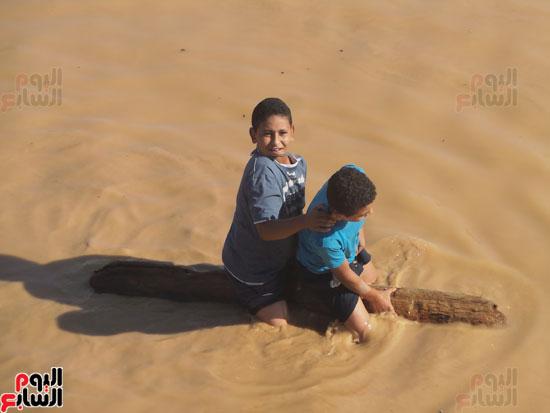 طفلان من القرية يركبون جذع نخلة للعبور بمياه السيول