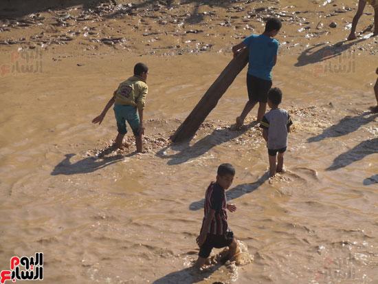 الأطفال يحملون جوع النخيل بعد اجتيازهم المياه