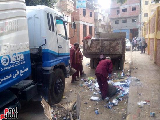 العمال في شارع دسق لرفع القمامة