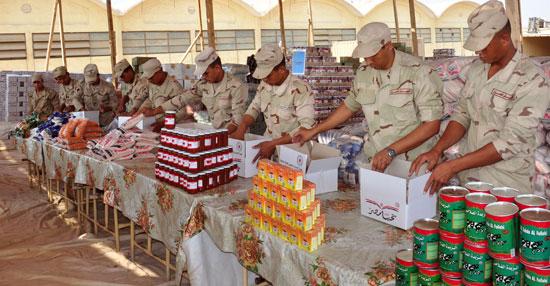 جنود القوات المسلحة يجهزون عبوات السلع المخفضة تمهيدًا لتوزيعها على المواطنين