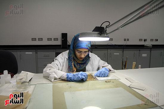 أخصائية الترميم أثناء ترميمها إحدى القطع الأثرية