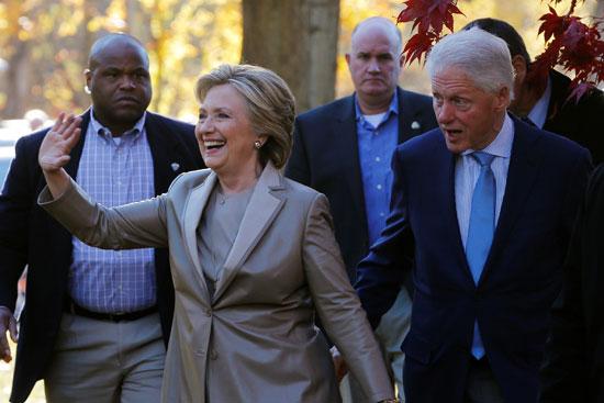 هيلارى تحى المواطنين لدى وصولها المقر الانتخابى بصحبه زوجها بيل كلينتون