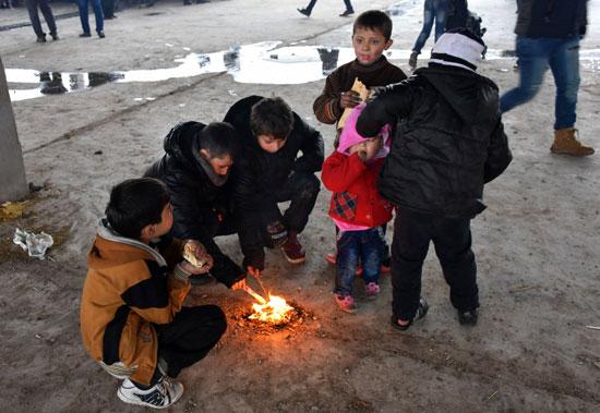 أطفال سوريين فروا من القصف يصطفون حول قطعة خشب مشتعلة للتدفئة