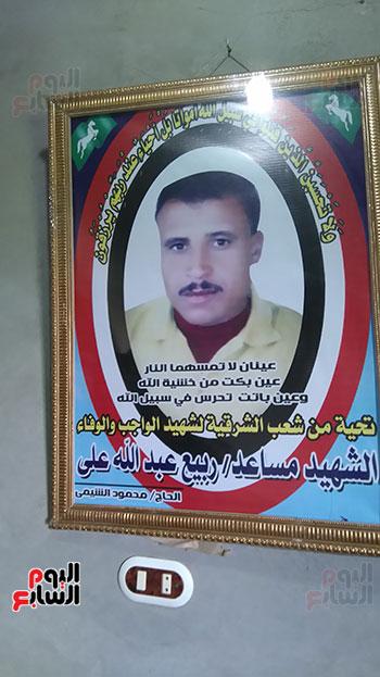 نجلة الشهيد تحمل صورة والدها وحفيد
