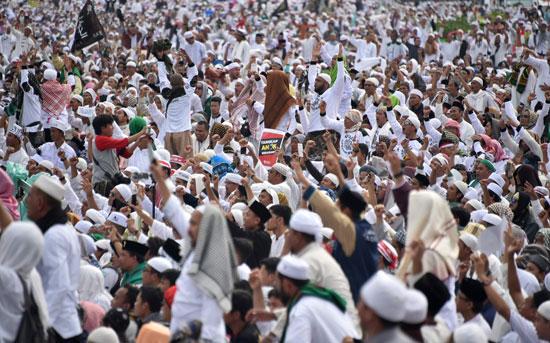 مواطن اندونيسى يقف وسط حشد من المتظاهرين