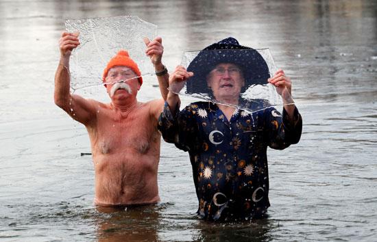 ألمان يرفعون قطع من الثلج أثناء السباحة فى المياه الباردة