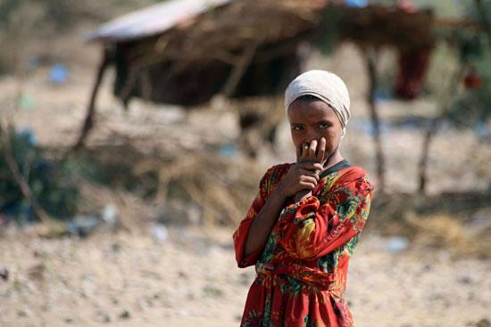 طفلة يمنية تقف داخل مخيم اللاجئين فى تعز