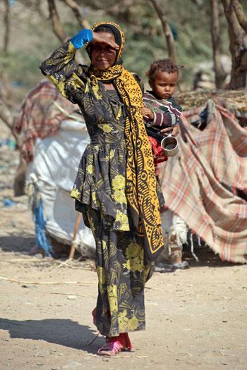 سيدة فى مدينة تعز تحمل طفلا وآثار الفقر تظهر عليهم