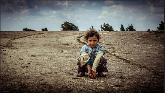 طفلة تجلس على الأرض