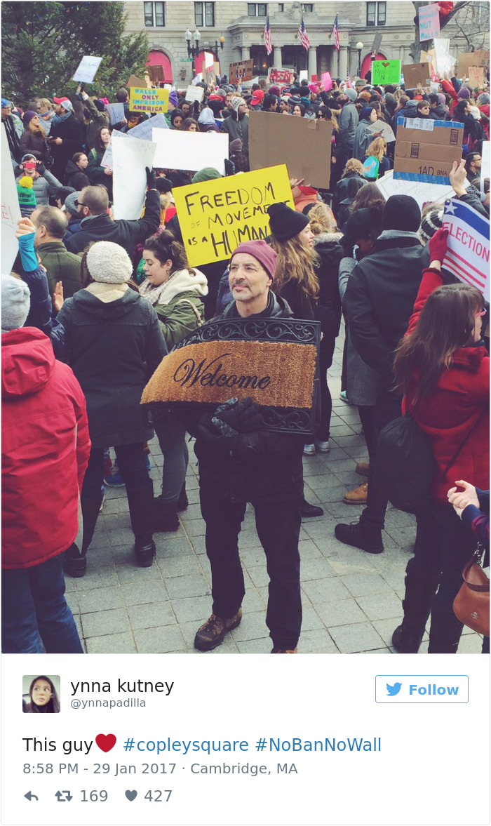 شاب يحمل لافتة مكتوب عليها مرحبا