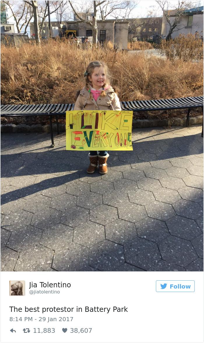 طفلة تحمل لافتة مكتوب عليها أنا أحب الجميع