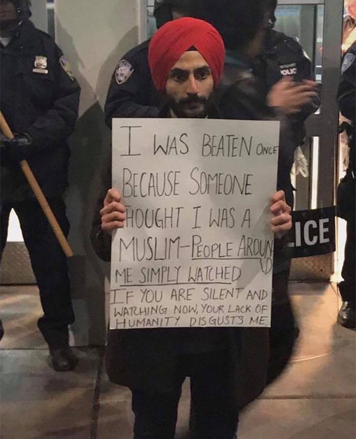 رجل يحمل لافتة مناهضة لقرار ترامب