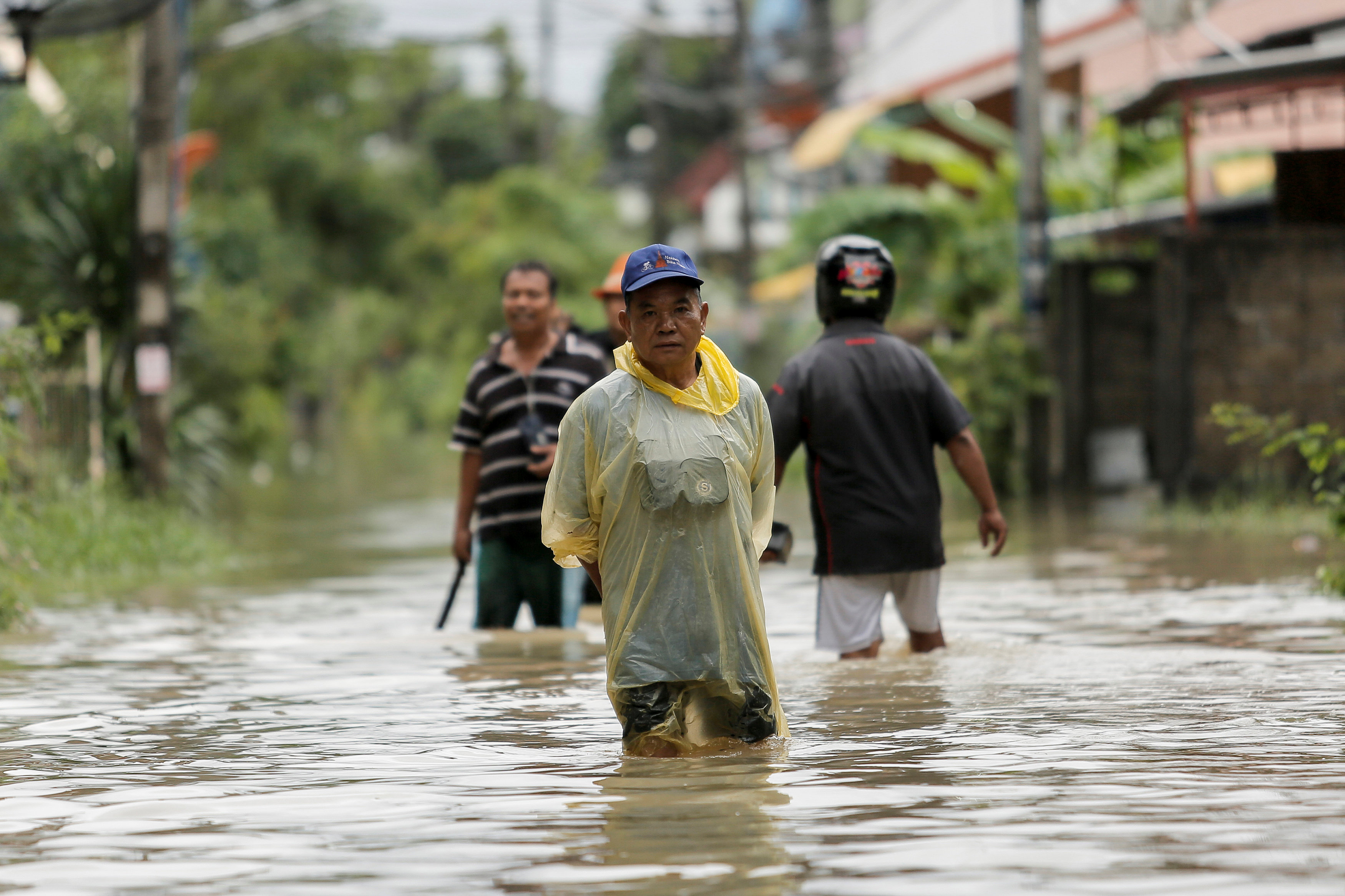 سكان يمشون فى مياه الفيضانات بشواع مقاطعة موانج فى تايالند - رويترز