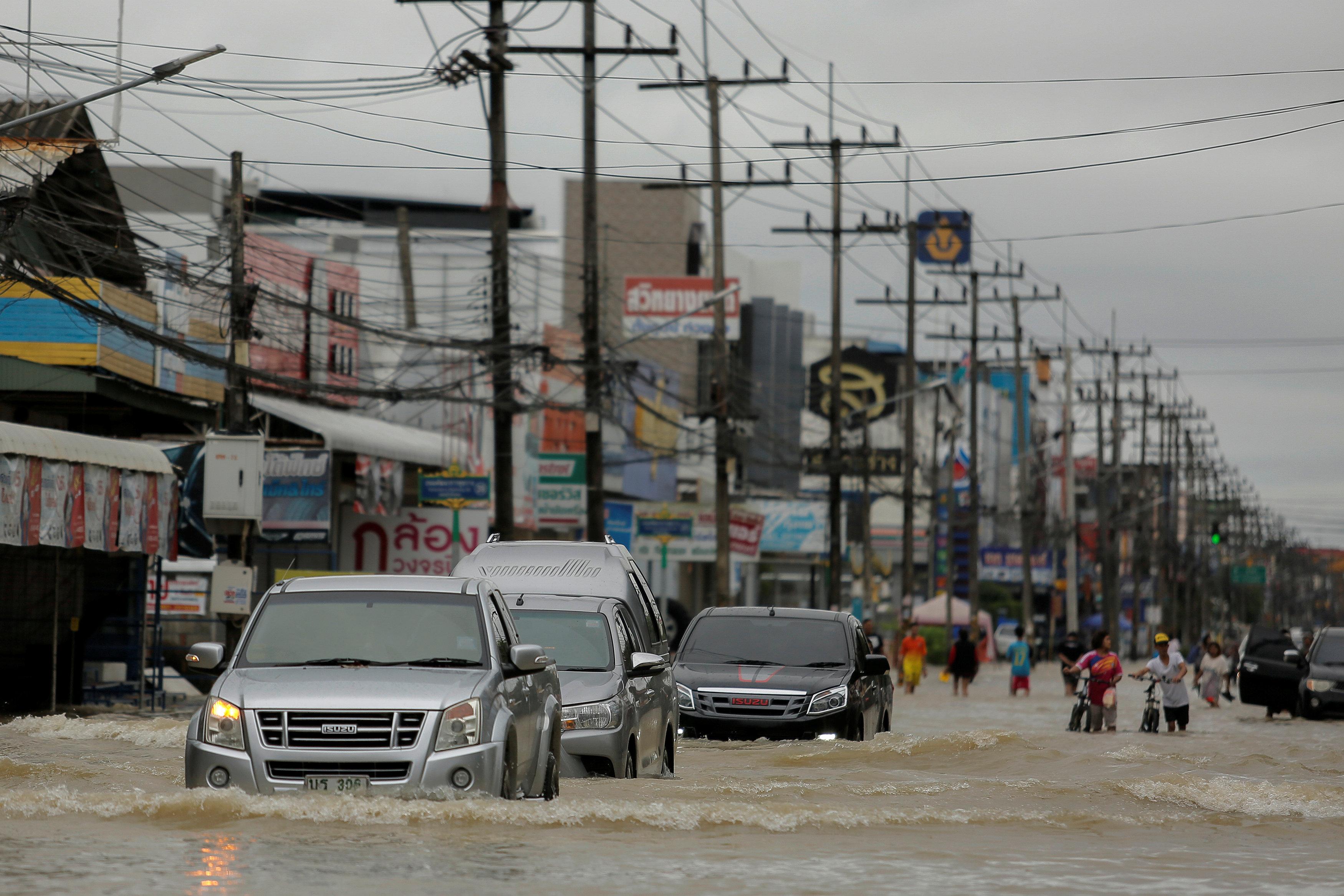 سيارات تسير فى مياه الفيضانات وسط شواع مقاطعة موانج - رويترز