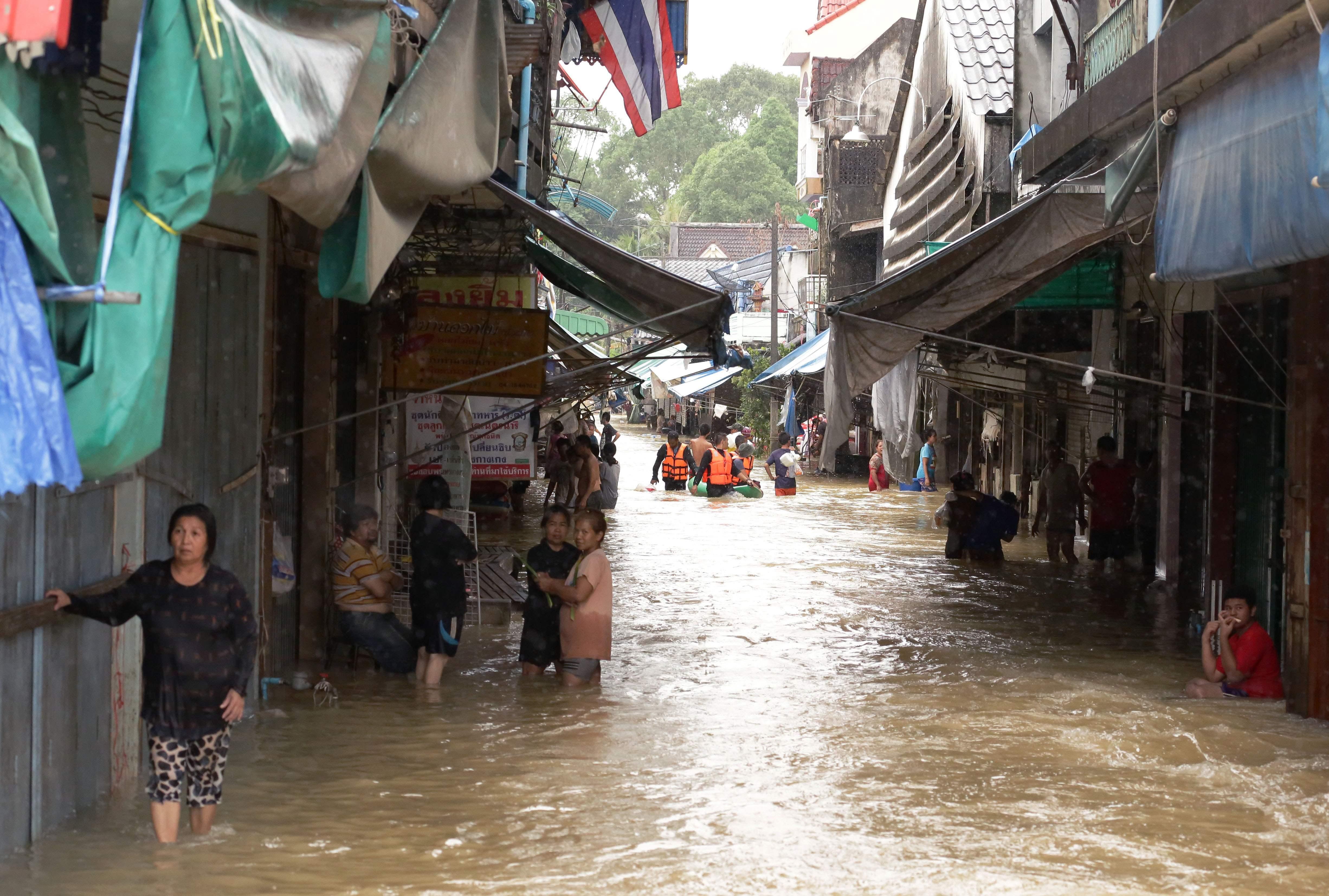سكان فى إحدى القرى فى تايلاند خارج يقفون خارج منازلهم بسبب فيضانات مياه الأمطار - أ ف ب