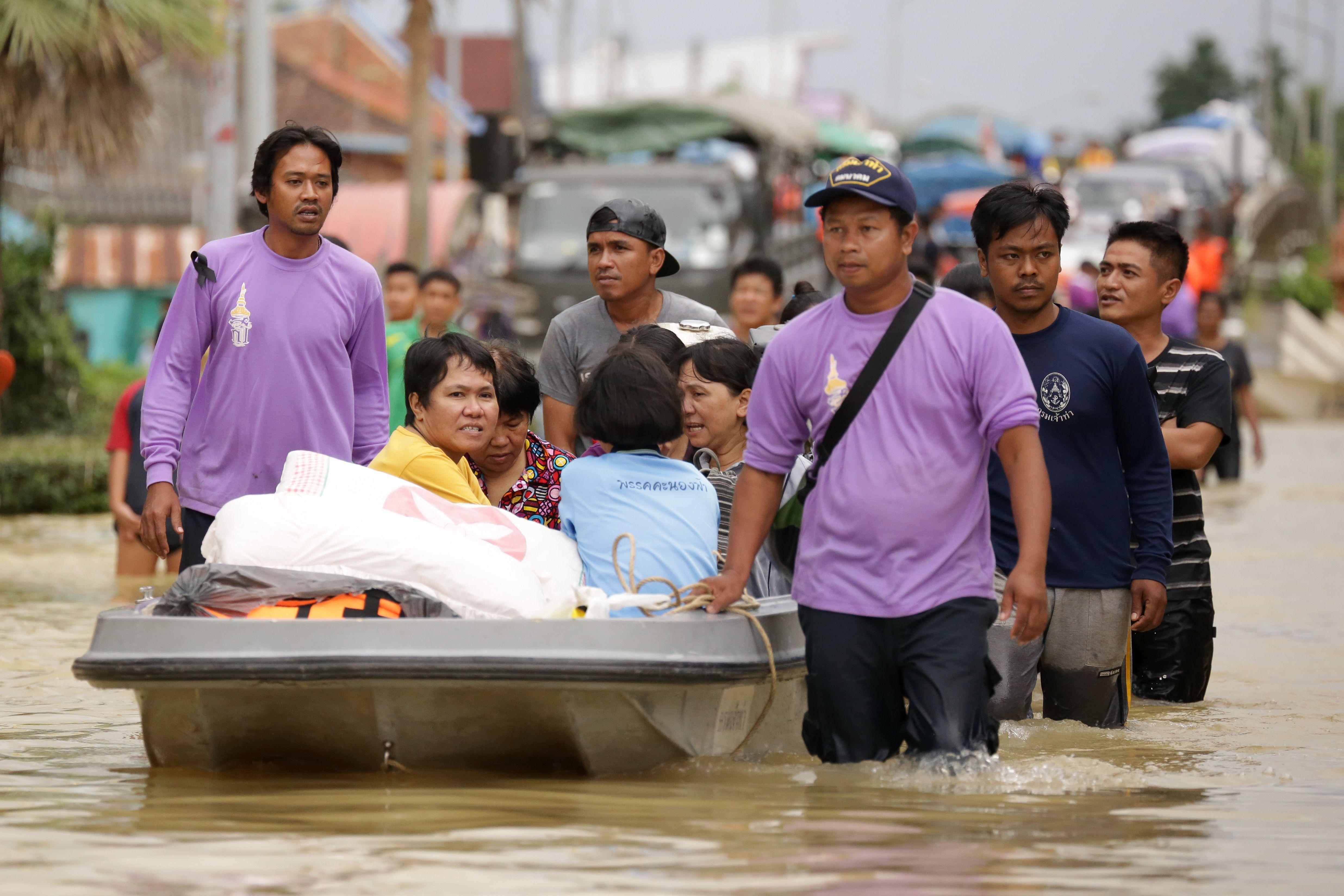 عمال الانقاذ يجلون عائلة من منزلها بسبب فيضانات فى تايلاند - أ ف ب