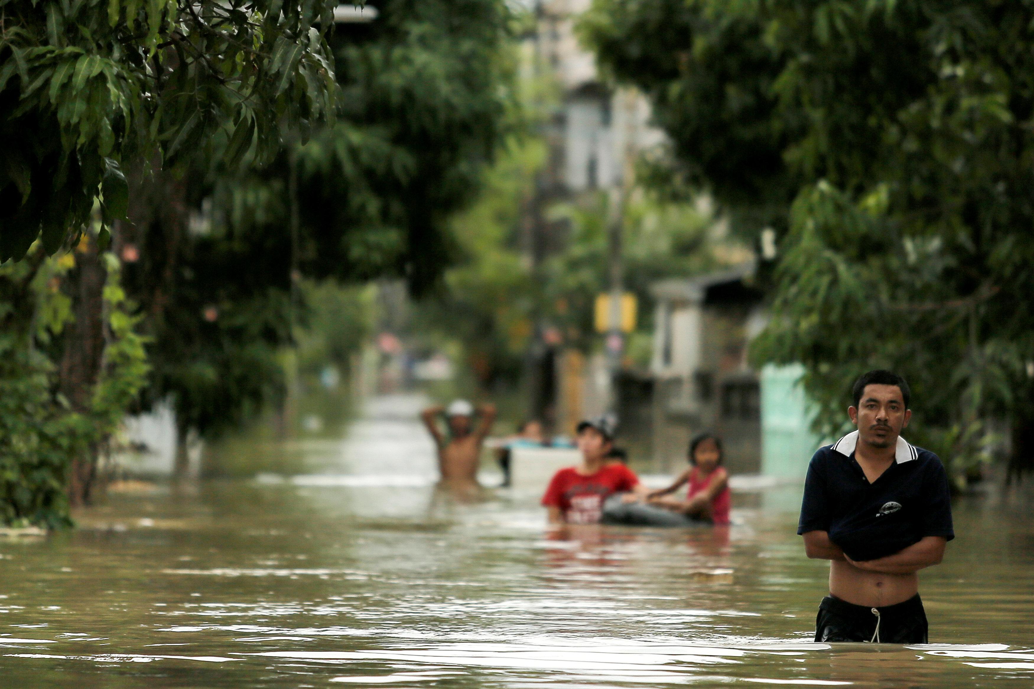 تايلانديون  يسيرون فى مياه الفيضانات