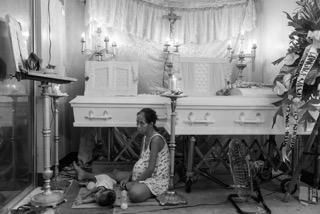 اليزابيث نافارو سيدة حامل تجلس بجانب نعش ابنها وزوجها يوم ١٤ ديسمبر الماضى