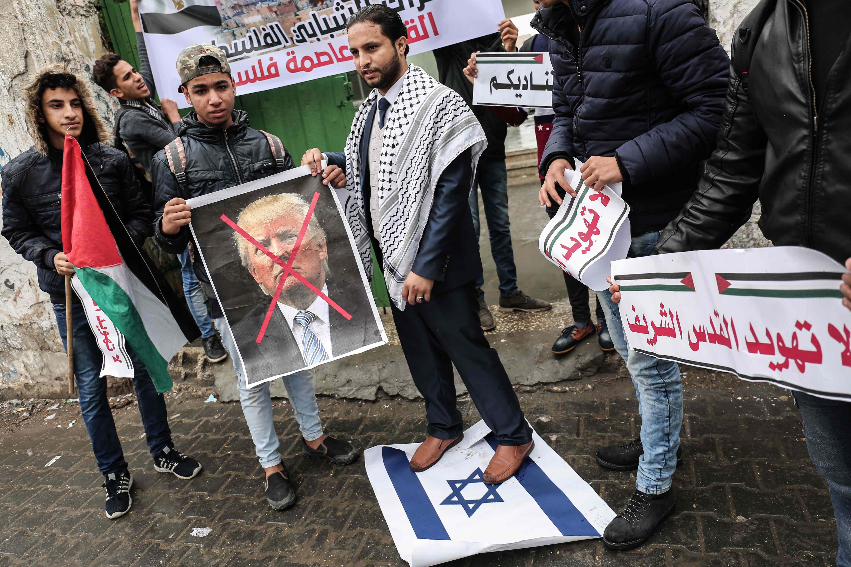 متظاهر يقف بقدمية على علم إسرائيل