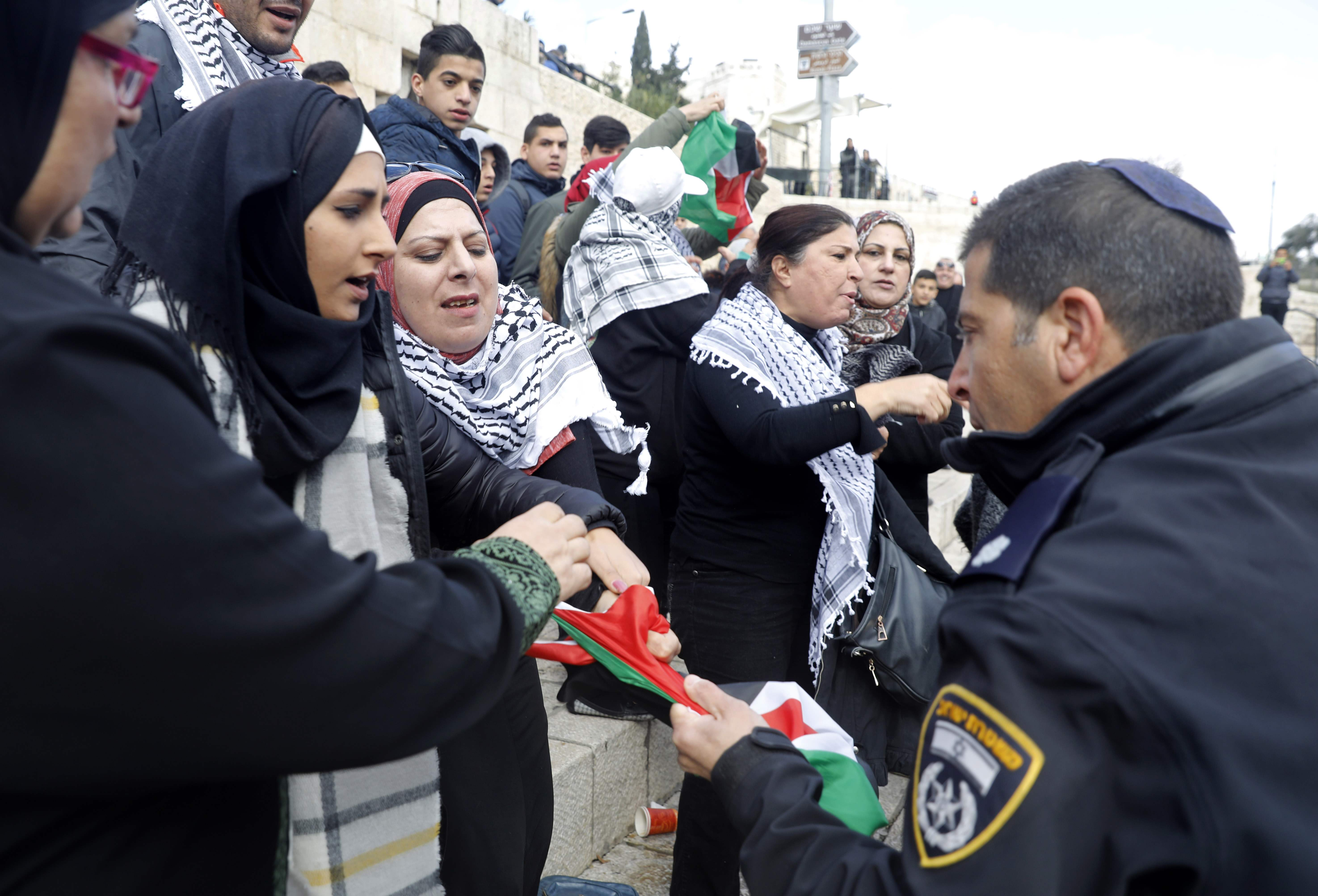أحد جنود الاحتلال يحاول الاستيلاء من سيدة فلسطينية على العلم الفلسطينى