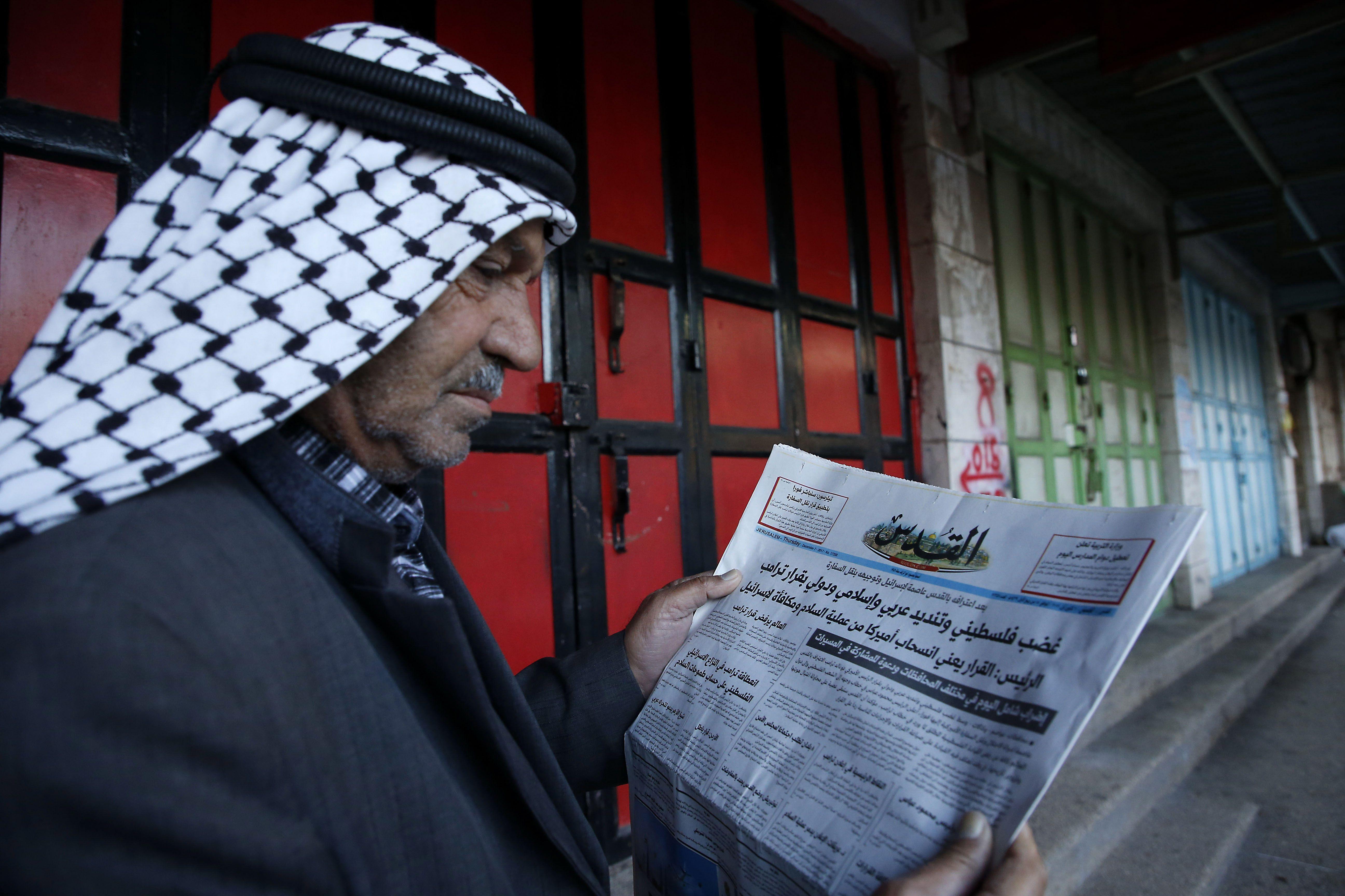 رجل فلسطينى يجلس أمام محله المغلق ويقرأ الجرايد