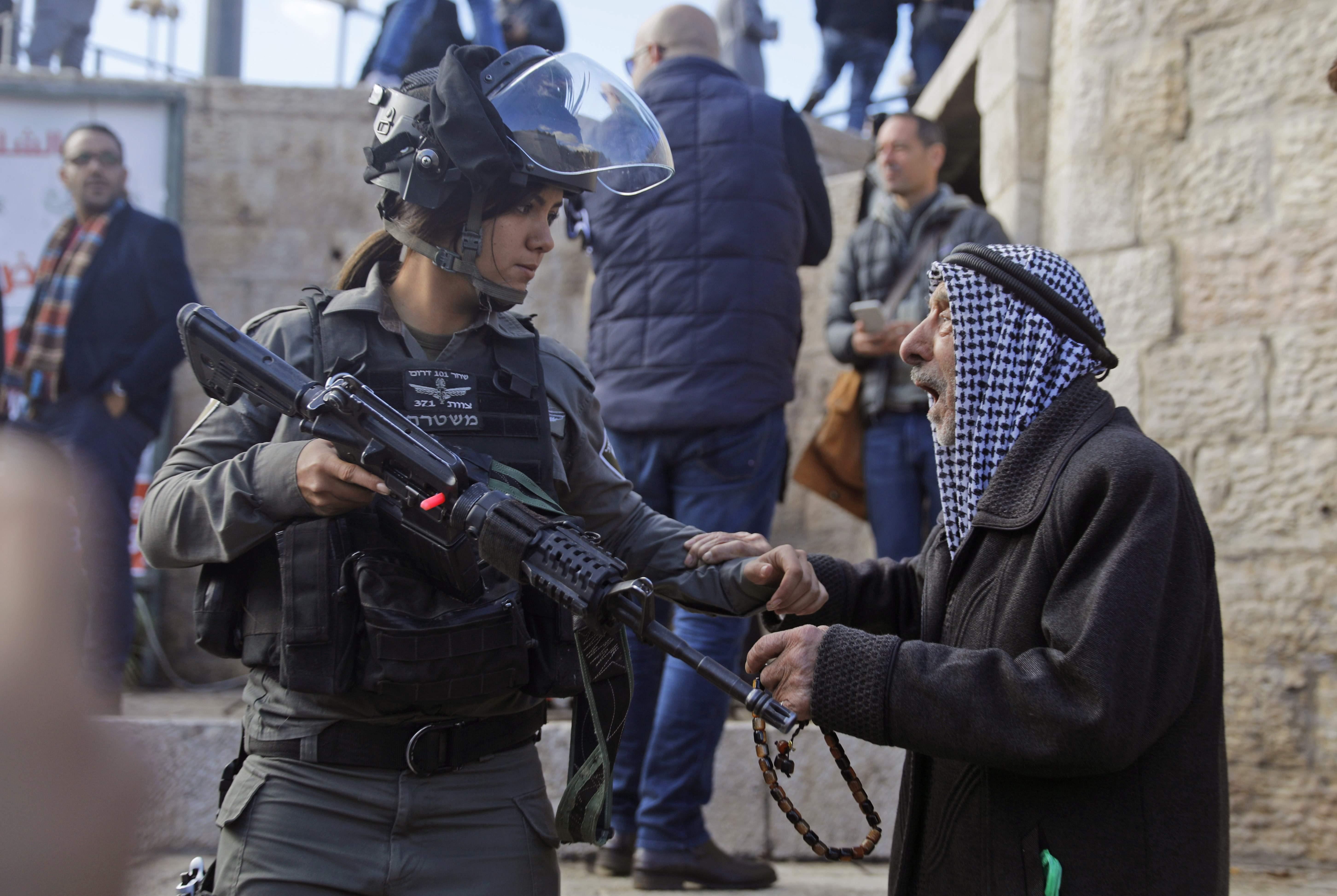 جندية اسرائيلية تشهر سلاحها على مسن فلسطينى