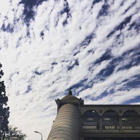 طالب يلتقط صورة لمبنى جامعة القارئ مع السحاب
