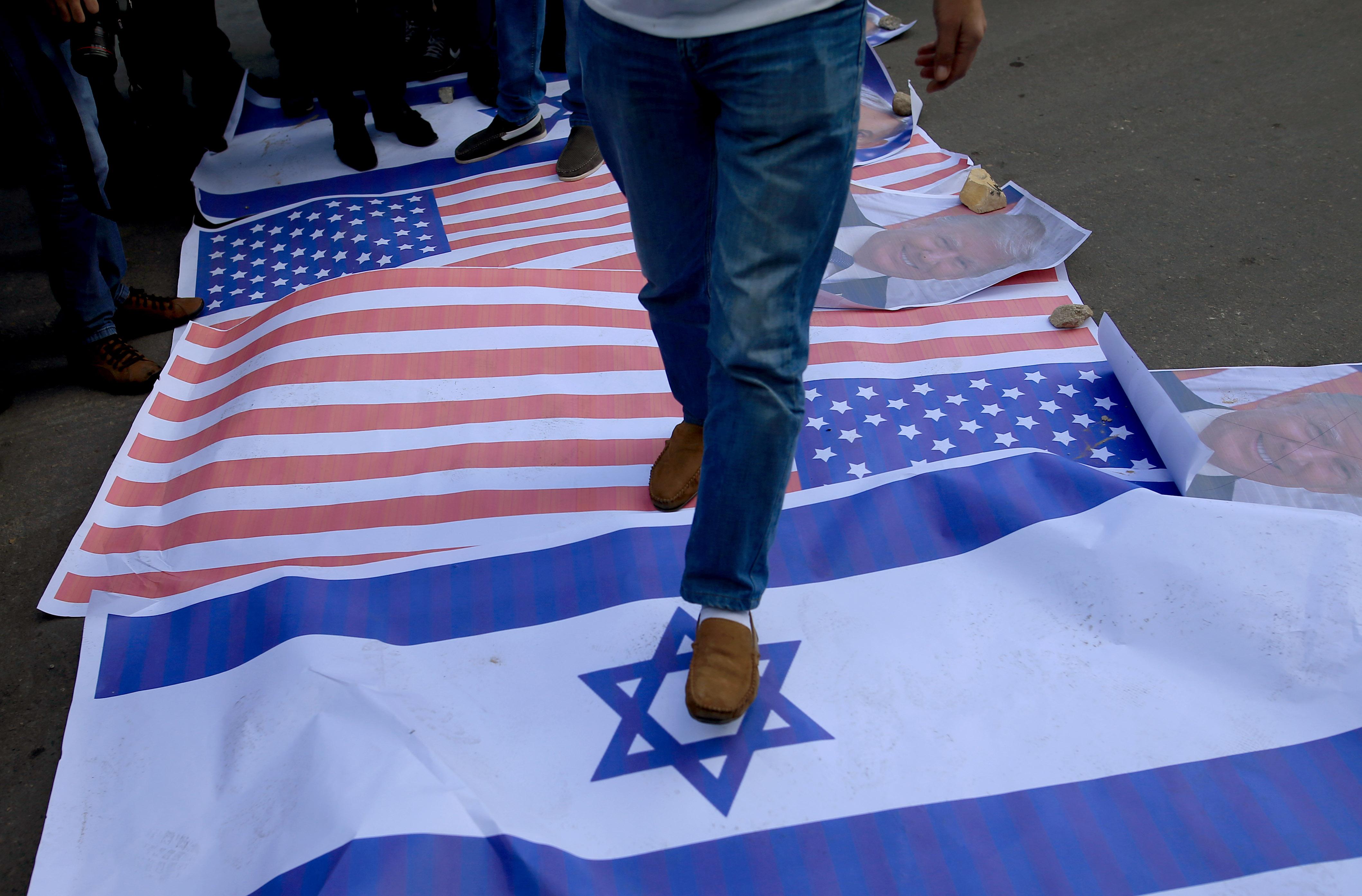 الفلسطينيون يدوسون بأقدامهم على العلم الاسرائيلى والأمر يكى