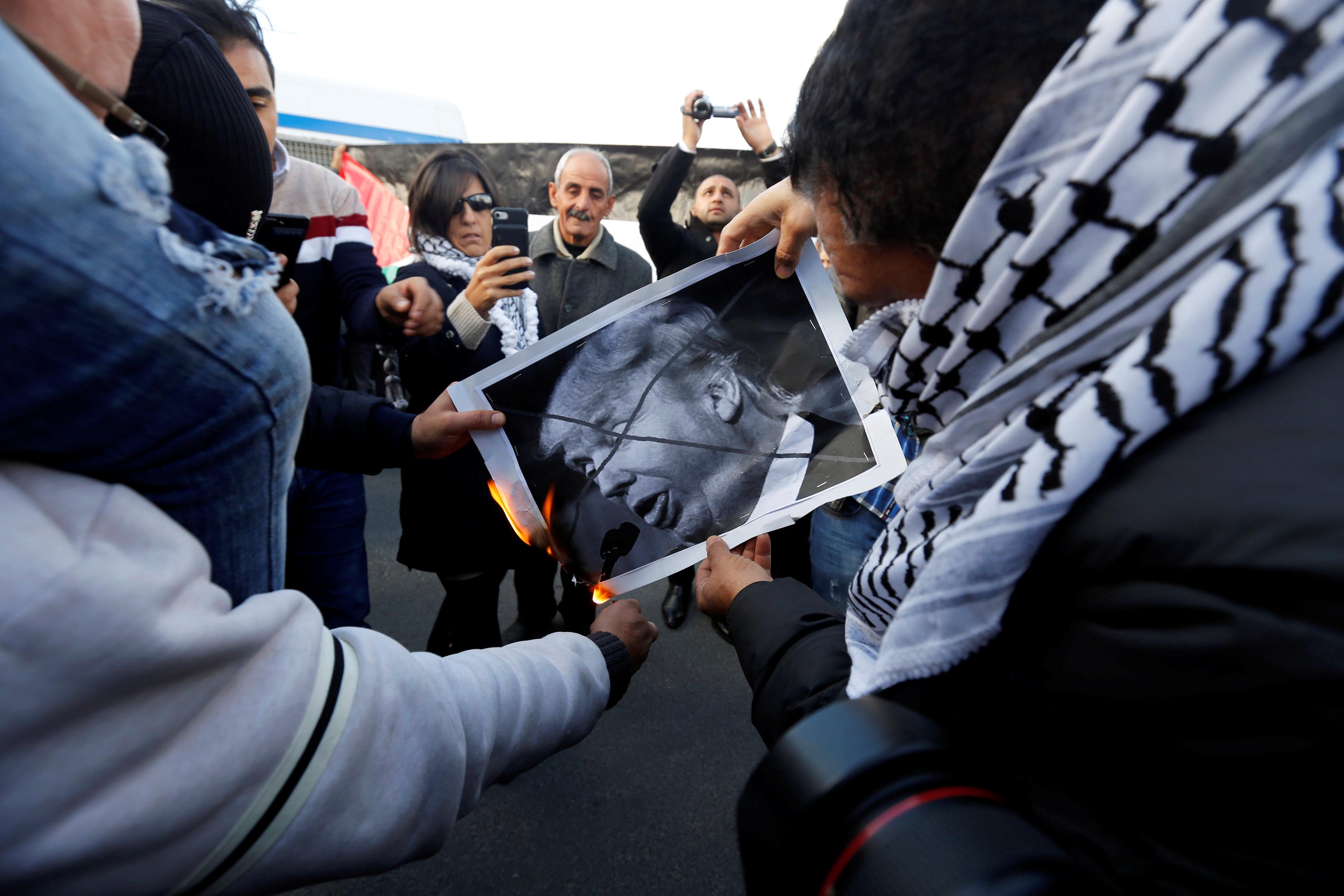متظاهرو عمان يشعلون النار فى صورة لترامب