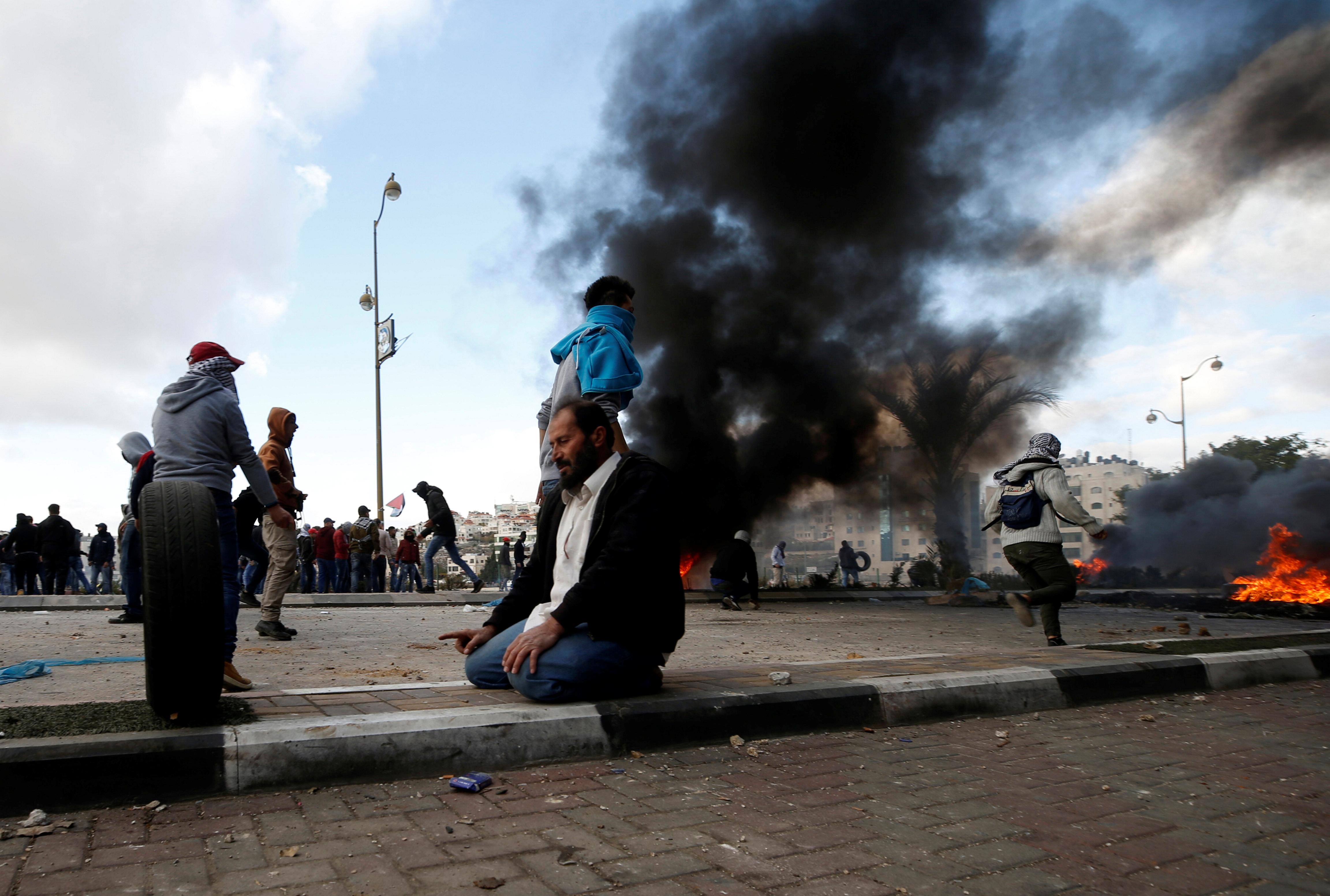 شاب فلسطينى يصلى خلال الاشتباكات