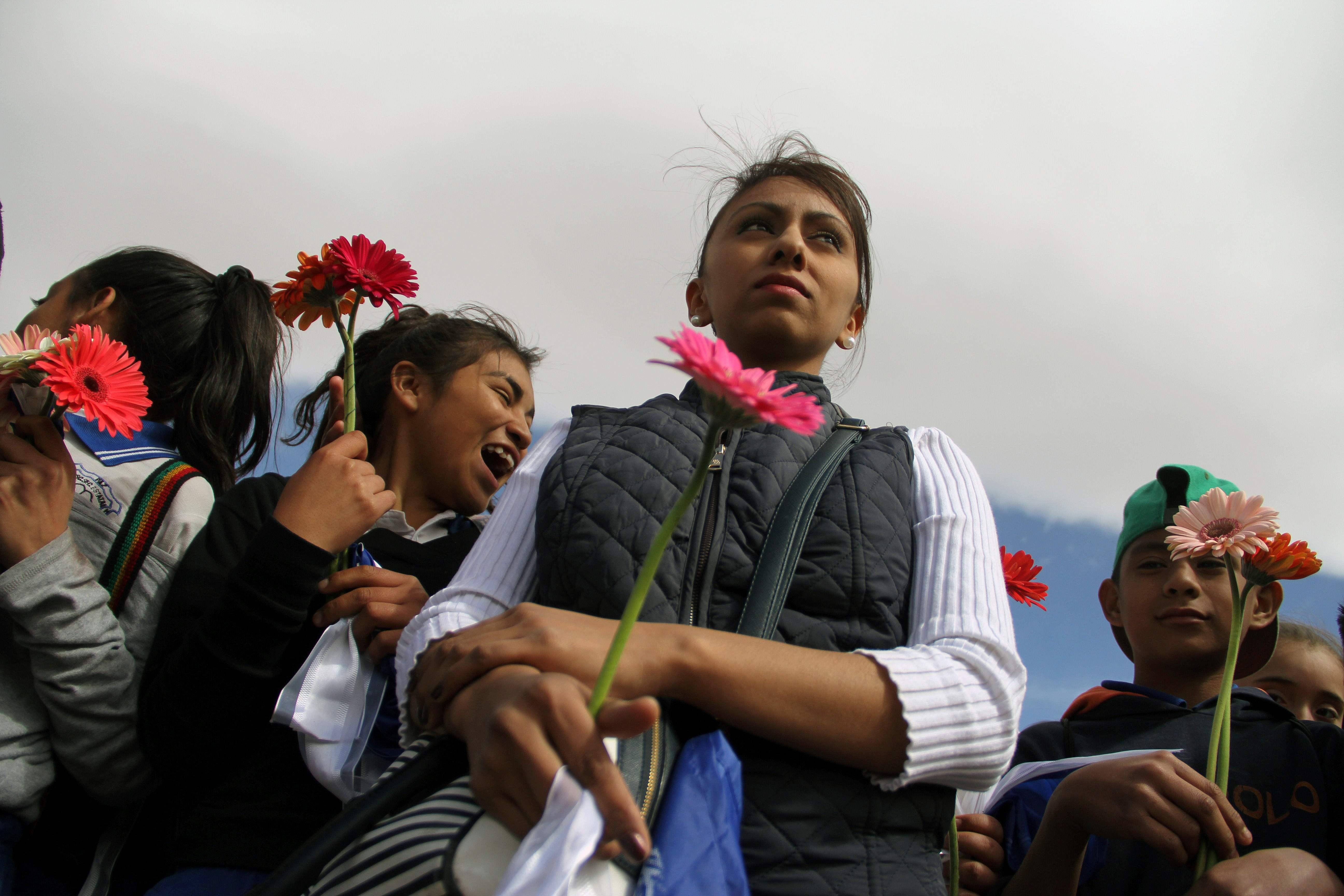 فتاة تحمل وردة وبجوارها اطفال يشاركون فى الوقفة الاحتجاجية ضد ترامب