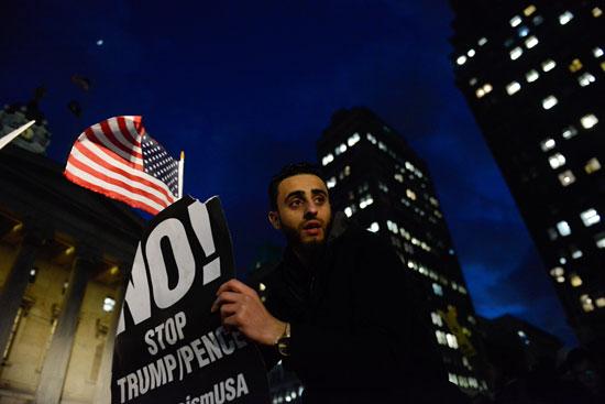 شاب يحمل لافتة منددة بقرار ترامب