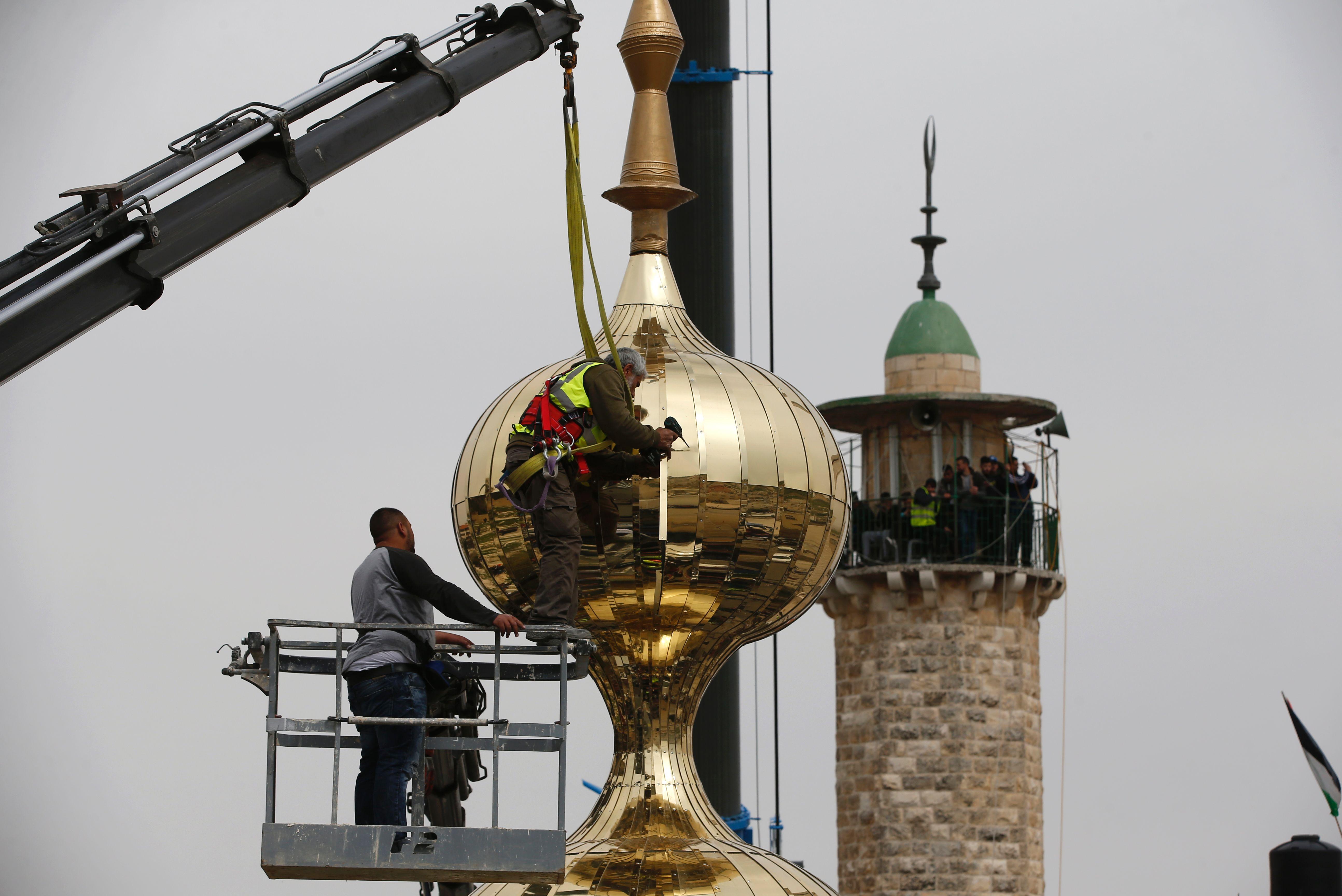 الفلسطينيون يرفعون الهلال للمئذنة لتثبيته