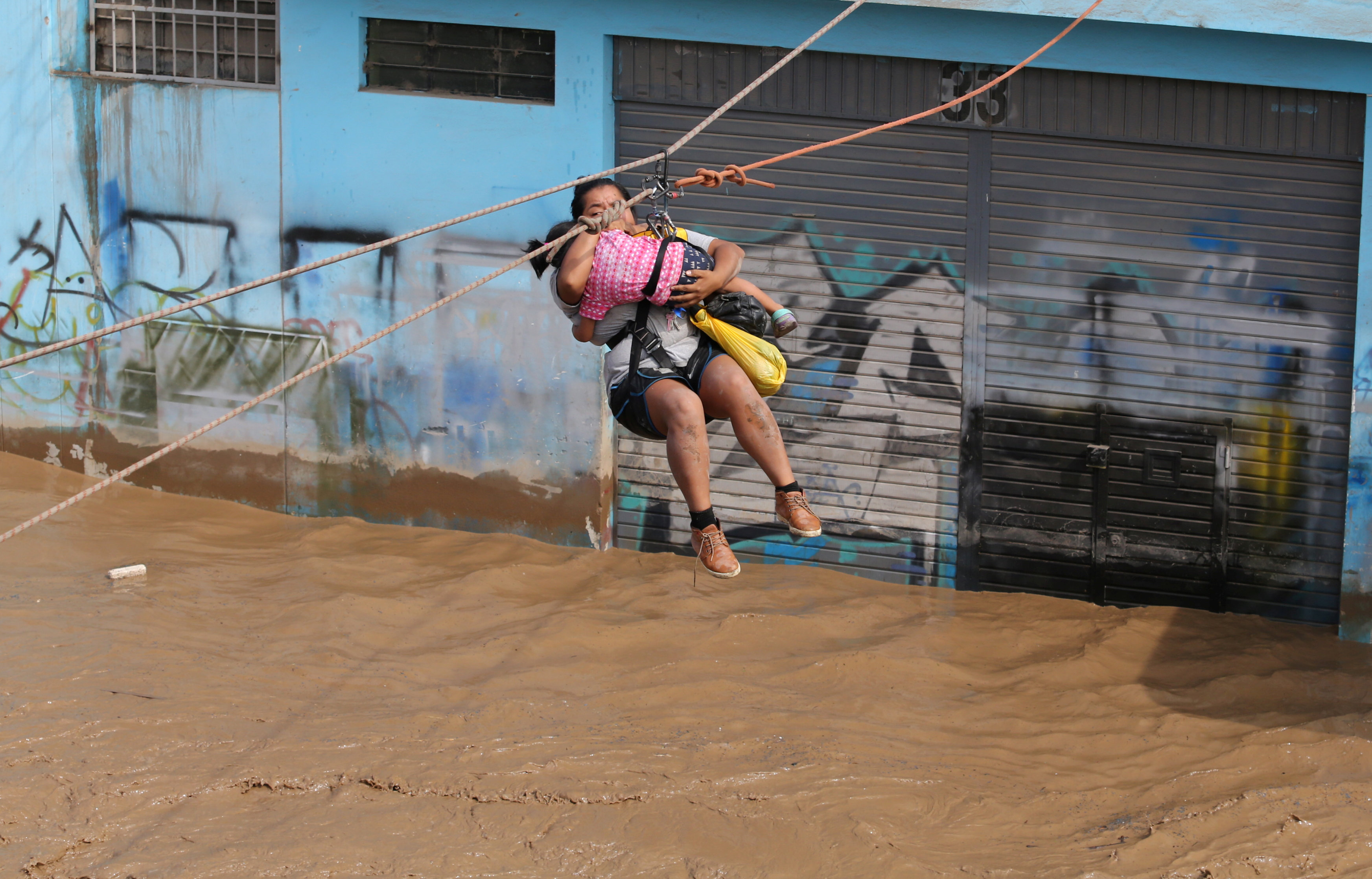 سيدة معلقة وسط مياه الفيضانات
