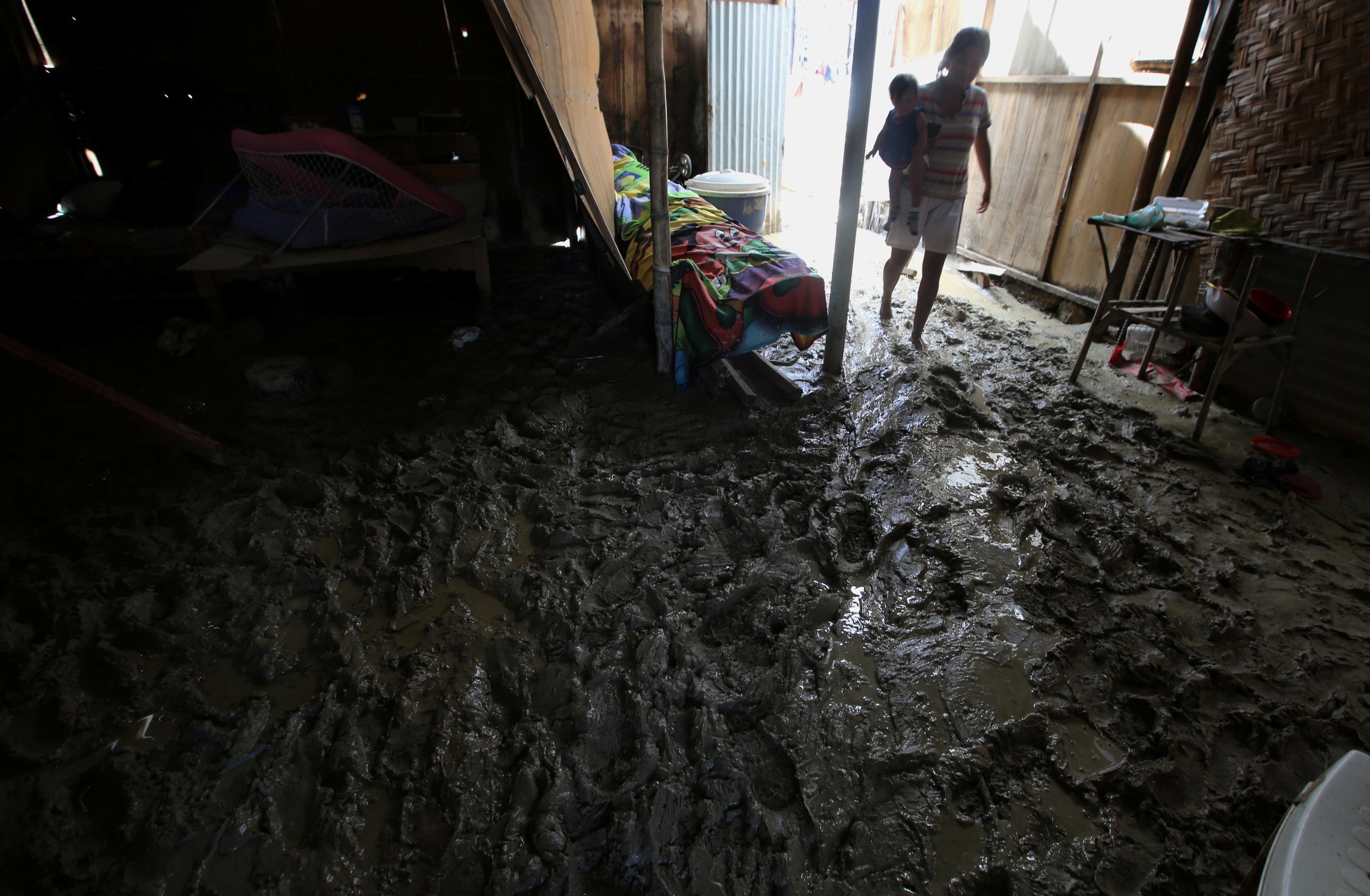 سيدة تحمل طفلها وسط مياه الفيضانات