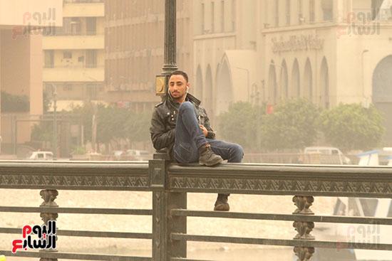 مواطن يجلس فوق سور كوبرى قصر النيل
