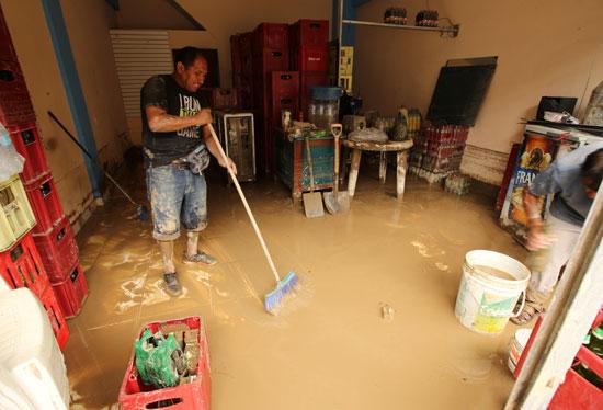 رجل يحاول تنظيف منزله من المياه والوحل