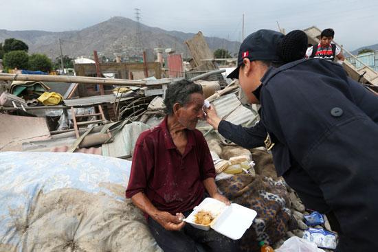إحدى الشرطيات تمسح دموع رجل مسن بعد ان دمر منزله مياه الفيضانات