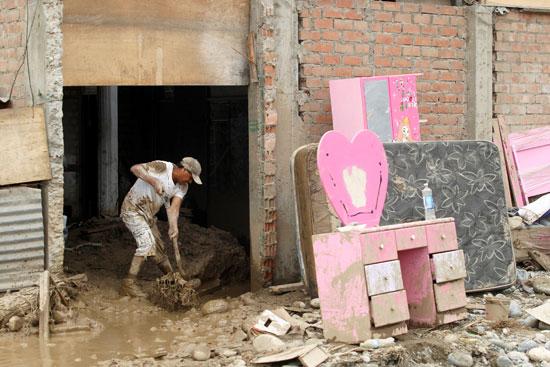 مواطنون يعبرون وسط بركة من المياه كونتها مياه الأمطار