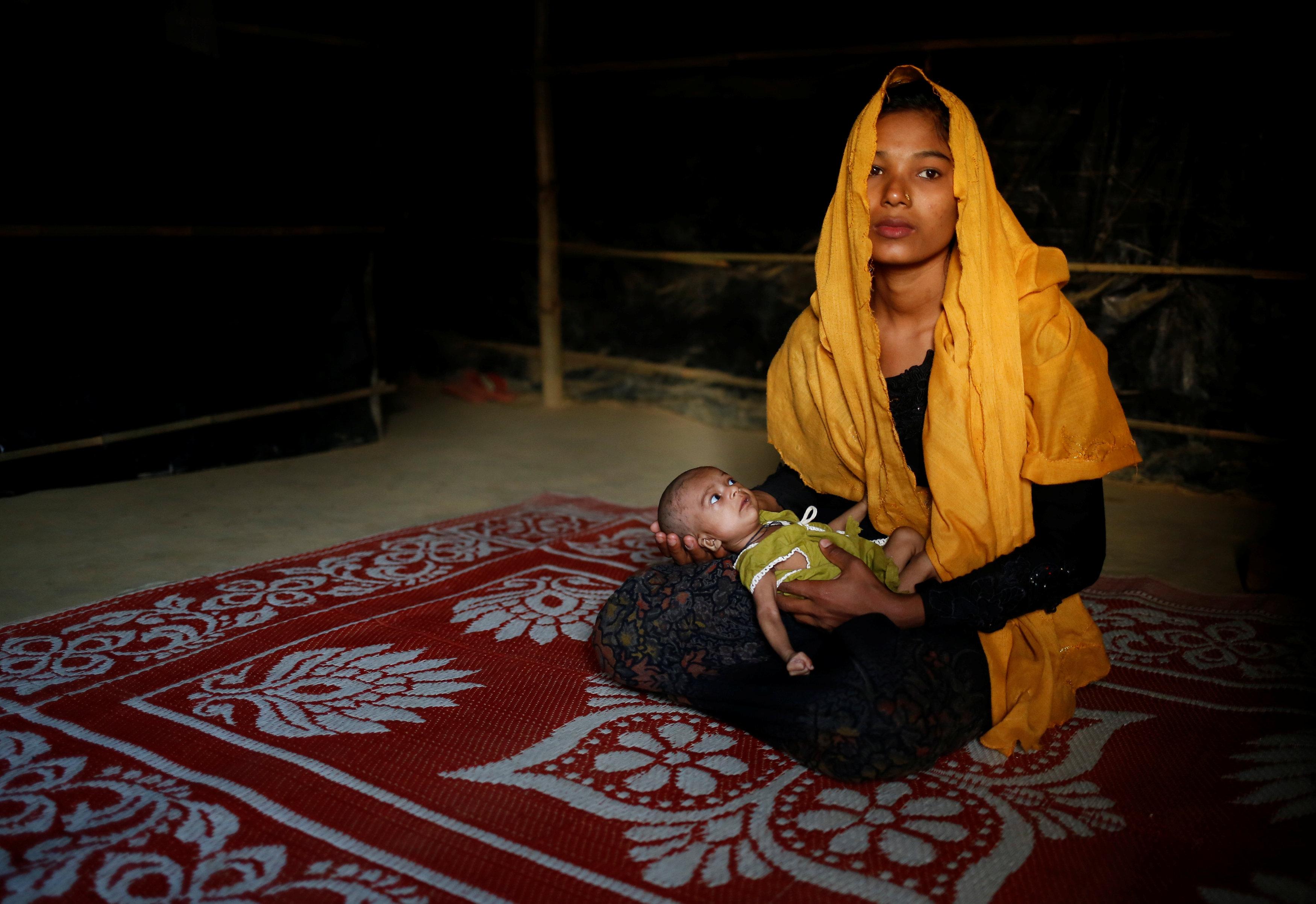 سيدة تحمل طفلها فى مخيم
